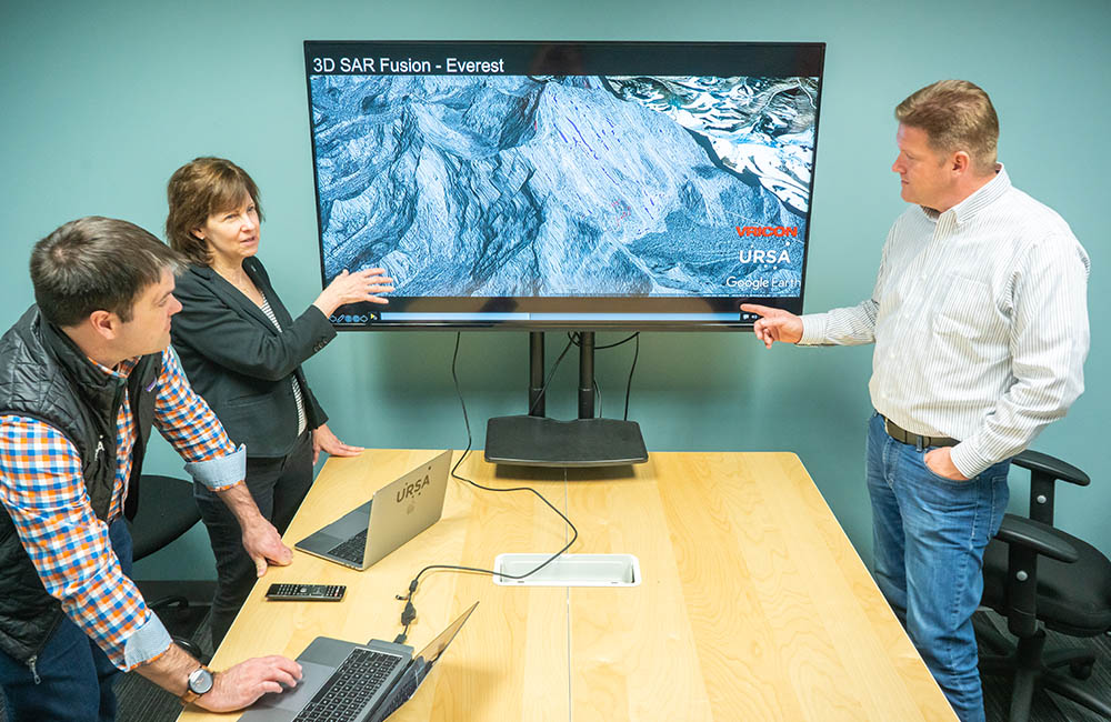 Ursa founders, Adam Maher, Julie Baker, and Derek Edinger, review a satellite image on a large monitor.