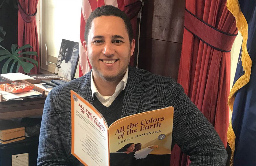Ithaca Mayor Svante Myrick holds the book All the Colors of the Earth.