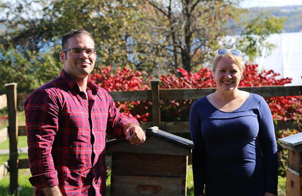 Nathan Oakes and Hailey Scofield of Combplex pose next to beehives at Wegmans Organic Farm.